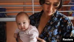 A single Tajik woman holds one of her twins in a shelter for women in crisis where she and other single women live outside Moscow.
