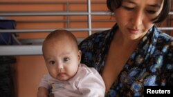 Женщина из Таджикистана с ребенком в кризисном центре для женщин на окраине Москвы. 16 октября 2011 года.