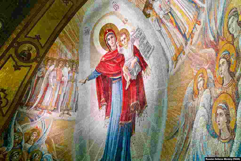 One of the numerous mosaics inside the cathedral shows Jesus being held by his mother, Mary. On April 24, the Russian news outlet MBK published leaked photos of unfinished mosaics inside the cathedral depicting Soviet leader Josef Stalin, Russian President Vladimir Putin, and scenes from Russia's 2014 takeover and annexation of Ukraine's Crimean Peninsula.