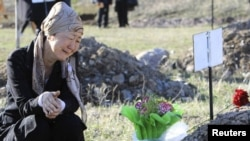 A woman mourns a victim of the violent revolt during a remembrance ceremony held at a cemetery in the village of Chon-Aryk.
