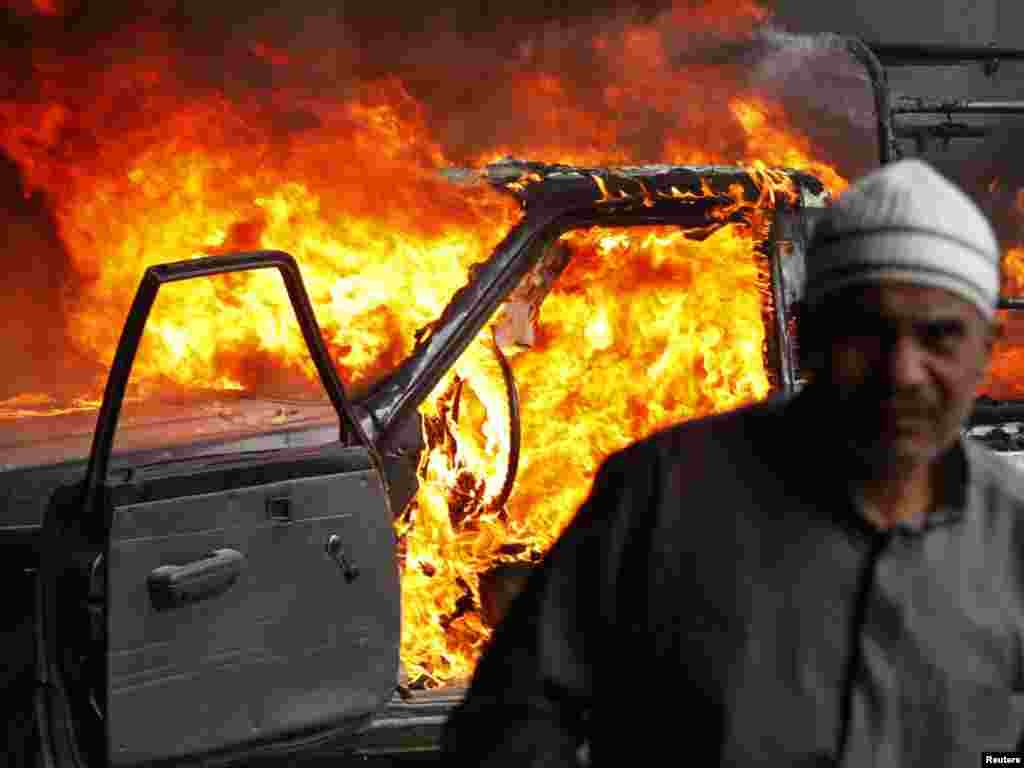 A protester walks in front of a burning police vehicle in Cairo on January 28.