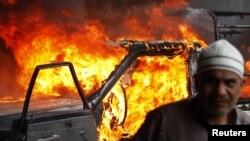 متظاهر مصري وخلفة سيارة تابعة للشرطة تحترق