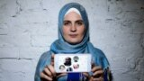 Mumine Saliyeva holding a picture of her imprisoned husband and their four children.