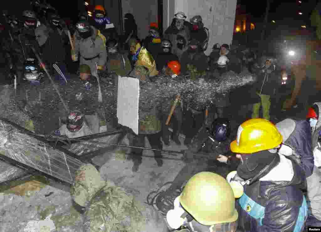 Полиция распыляет воду против демонстрантов.