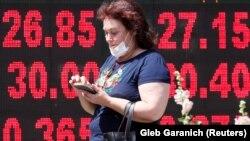 Жінка в захисній масці проходить повз пункт обміну валют, Київ, 2 липня 2020 року