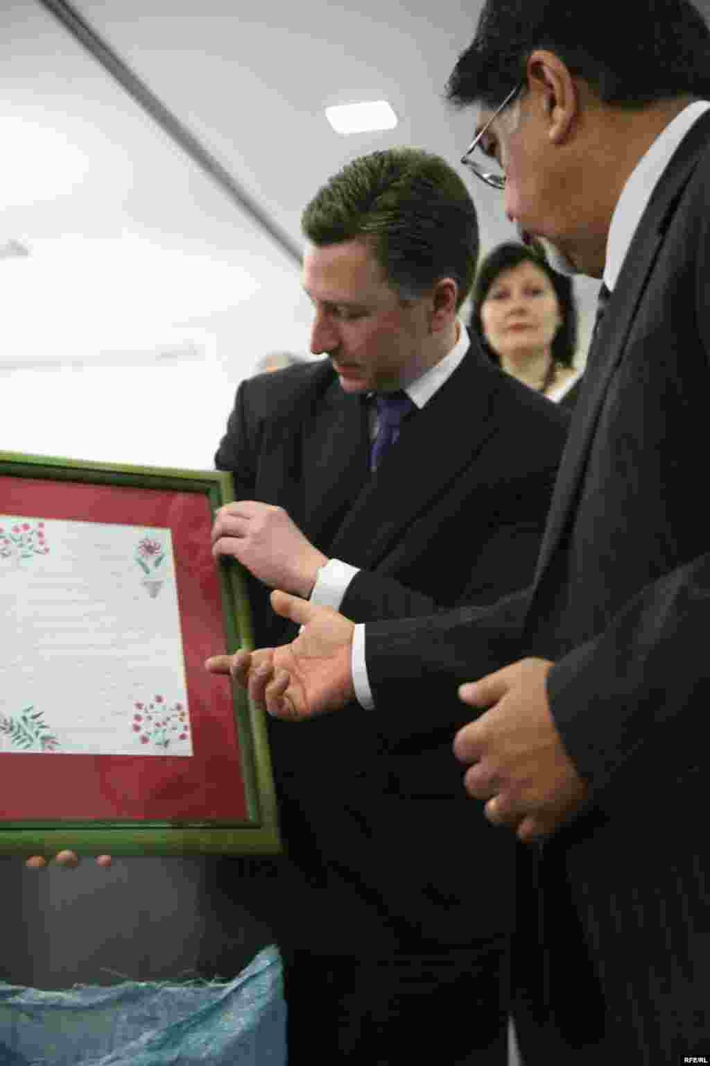 The Ambassador is presented with a framed letter from a Radio Free Afghanistan listener