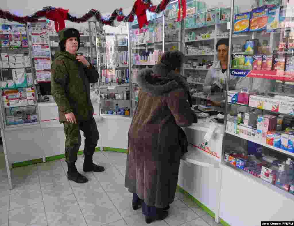 A young Russian soldier waits his turn inside a pharmacy in the center of Gyumri.