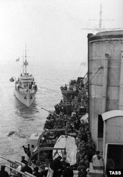 До борту крейсера «Червоний Крим» Чорноморського флоту підходить тральщик для перекидання на берег десанта. Крим, 1942 рік