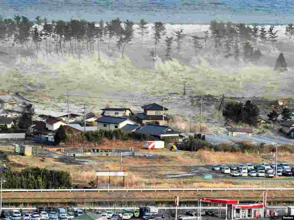 A massive tsunami engulfs a residential area after a powerful earthquake in Natori, Miyagi prefecture in northeastern Japan.Photo by Reuters