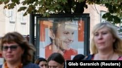 """Киевляне на фоне билборда лидера """"Голоса"""" Святослава Вакарчука."""