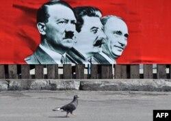 Украина астанасы Киевтің орталық алаңындағы сурет. Плакатта (солдан оңға қарай) Адольф Гитлер, Иосиф Сталин және Ресей президенті Владимир Путин. 28 шілде 2014 жыл.