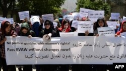 Afghanistan -- University students and independent civil society activists take part in a demonstration in support of passing the Elimination of Violence against Women law in front of Parliament in Kabul May 27, 2013.