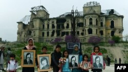 Children displaying photos of war victims stand in front of the damaged Darul Aman Palace just outside of Kabul, which was one of the area's many casualties, before its reconstruction.