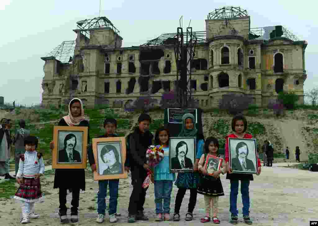 Afghan children pose for a photograph holding images of victims of war during a memorial ceremony in front of the destroyed palace of Darul Aman in Kabul on April 25. (AFP/Wakil Kohsar)