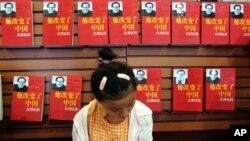 یک زن چینی جلوی غرفه ناشر کتاب «مردی که چین را تغییر داد» در نمایشگاه کتاب شانگهای در سال ۲۰۰۵