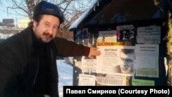 Павел Смирнов рядом с объявлением о митинге