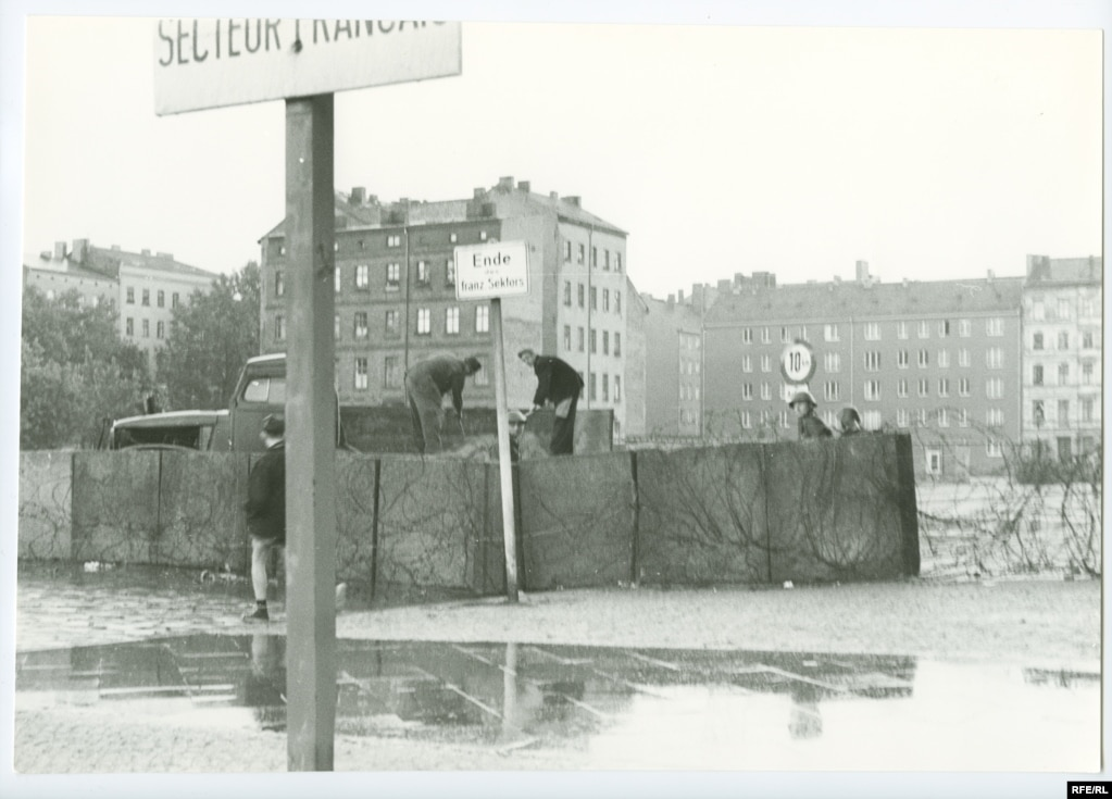 Поліція НДР охороняє перший відсік Берлінського муру. Комуністичний керівник НДР тих років Вальтер Ульбріхт за два місяці до цього заявляв, що ніякої стіни ніколи побудовано не буде. У ніч на 13 серпня 1961 року, коли почалося будівництво, він назвав це «антифашистським захисним бар'єром»