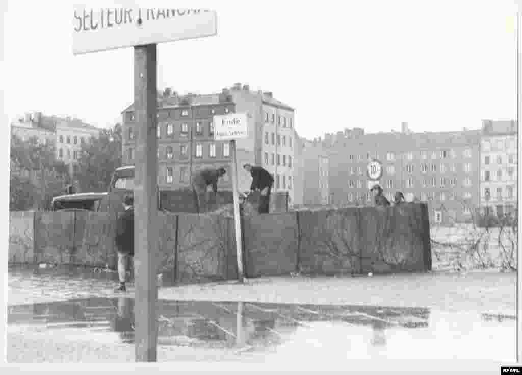 "East German police patrol a temporary, prefabricated section of the Berlin Wall. - After midnight on August 13, East German troops began erecting what Communist East German leader Walter Ulbricht called an ""anti-fascist protection barrier."" On June 15 of that year, he had declared: ""Nobody intends to build a wall."""