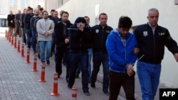 This image obtained from Dogan News Agency (DHA) shows Turkish police officers escorting people after their arrest for alleged links with US-based Muslim cleric Fethullah Gulen on April 26, 2017. File photo