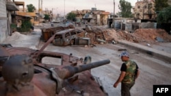 A member of the Free Syrian Army walks past a destroyed government tank in the town of Atareb in northern Aleppo province.