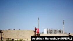 Жители села Акай попадают в закрытый город Байконур, перелезая через бетонное ограждение. Кызылординская область, 14 июля 2013 года.