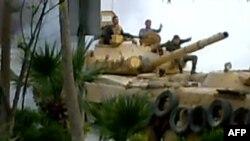 Ushtarët sirainë duke patrulluar me tank, në rrethinën e Damaskut, 12 prill, 2012