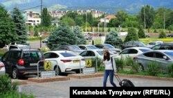 Алматыдағы көлік тұрағының жанынан өтіп бара жатқан адам. Көрнекі сурет.
