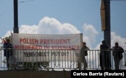 Люди во время выступления Дональда Трампа на мосту держат баннер, в котором утверждается, что президента Польши убили в России. Имеется в виду Лех Качинский, погибший авиакатастрофе в 2010 году под Смоленском в России.