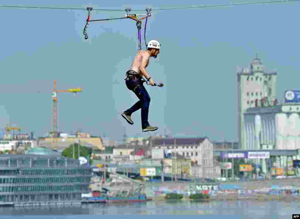 A man hanging by his skin crosses the Dnipro River on a 552-meter-long cable between the two banks of the water in Kyiv on May 23. (AFP/Sergei Supinsky)