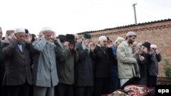 Чечня - Мужчины молятся над телом Заремы Садулаевой перед ее похоронами в селе Шалажи, 11.08.2009