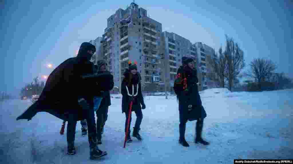 Учасники різдвяного вертепу з авдіївського осередка скаутської організації «Пласт» йдуть колядувати у стару частину міста повз розбиті боями дев'ятиповерхівки на околиці Авдіївки, 7 січня 2019 року