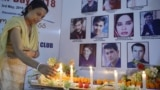 An Indian journalist lights candles during a vigil for Afghan journalists killed in a targeted earlier this year.