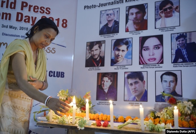 An Indian journalist lights candles during a vigil for 10 Afghan journalists who were killed in separate attacks in late April in Kabul.