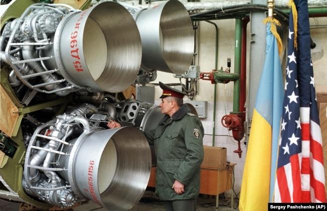 Український офіцер оглядає ракету УР-100Н перед її демонтажем. Дніпро, 26 лютого 1999 року. Ракету було знищено в рамках відмови України від ядерної зброї, що було обумовлено Будапештським меморандумом, підписаним у 1994 році. Згідно із цим Меморандумом США, Росія і Велика Британія зобов'язалися поважати незалежність, суверенітет та існуючі кордони України