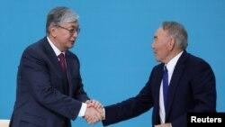 """Қасым-Жомарт Тоқаев (сол жақта) және Нұрсұлтан Назарбаев """"Нұр Отан"""" партиясы съезінде. Нұр-Сұлтан, 23 сәуір 2019 жыл."""