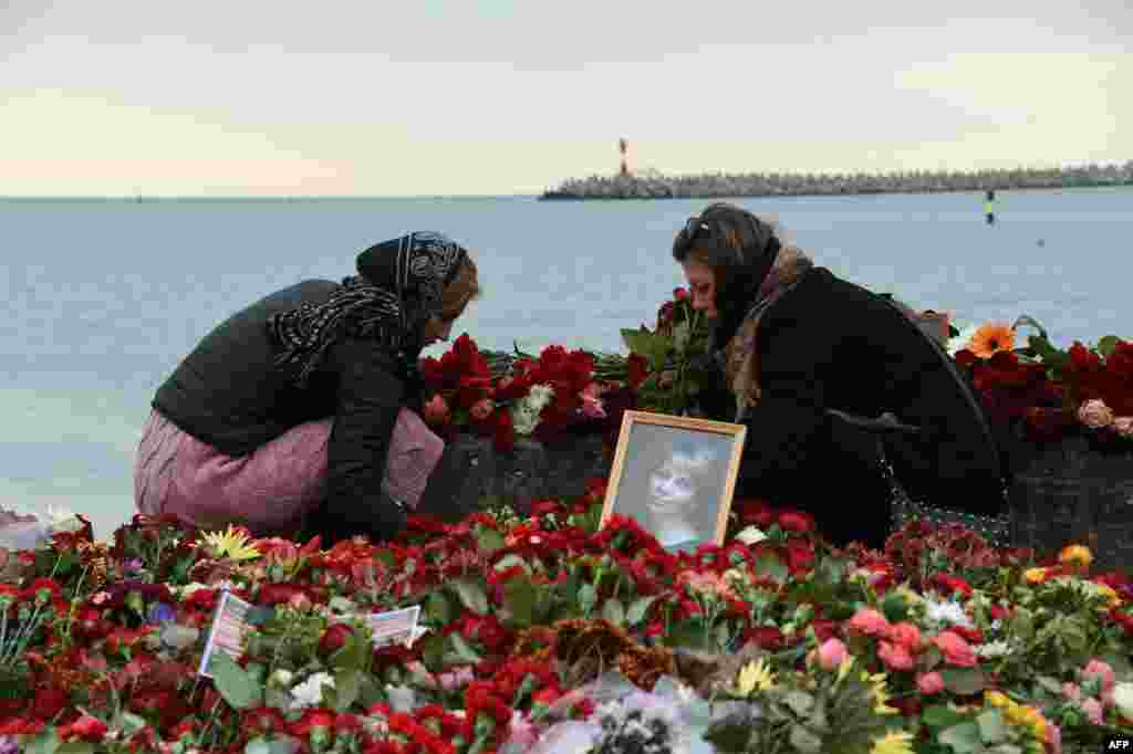People lay flowers next to a portrait of famed Russian charity activist Elizaveta Glinka (known as Dr. Liza) at a makeshift memorial on the shore of the Black Sea in Sochi, Russia, after a military plane carrying Glinka and 91 others crashed into the Black Sea. (AFP/Vasily Maximov)