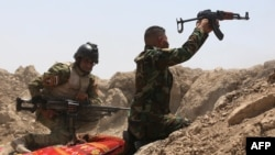 Iraqi soldiers fire toward Islamic State (IS) militants outside Ramadi on May 19. An Iraqi soldier describes how he and his comrades were left isolated in Ramadi.