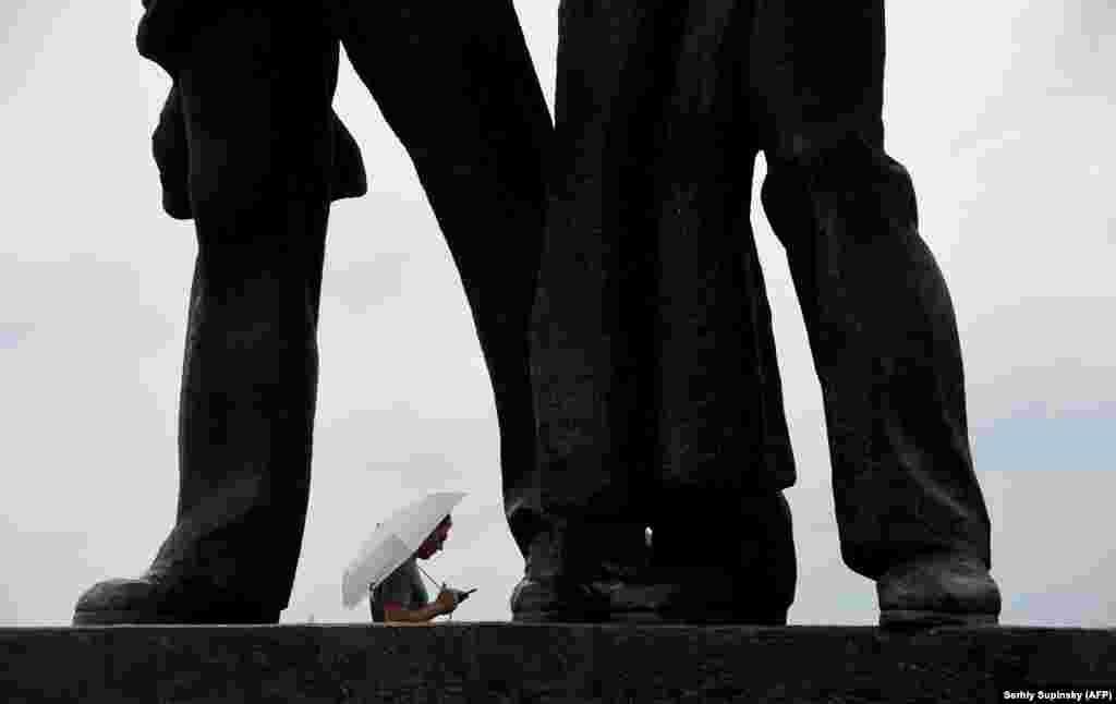 A man stands under an umbrella beneath a Soviet-era monument as rain falls in the Ukrainian capital, Kyiv. (AFP/Sergei Supinsky)