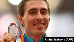 Sergei Shubenkov poses on the podium with the silver medal he won in the 110-meter hurdles event at the 2017 IAAF World Championships in London, where he competed as a neutral athlete.