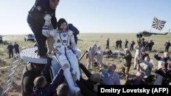 Сотрудники Роскосмоса помогают Норишиге Канаи выбраться из капсулы после приземления. Карагандинская область, 3 июня 2018 года.