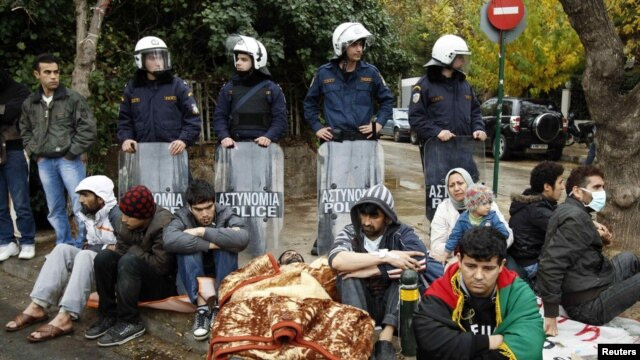 A group of Iranian refugees, some of them with their mouths sewn shut, protest outside the UN refugee agency office in Athens demanding asylum.
