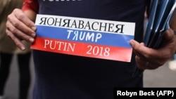 Američki demonstrant drži transparent sa bojama ruske zastava na kojem piše Rorabaher, Tramp i Putin