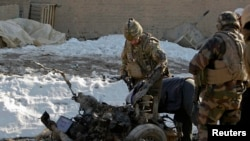 NATO troops investigate the the wreckage of a suicide bomber's car at the site of an attack in Kabul earlier this month.