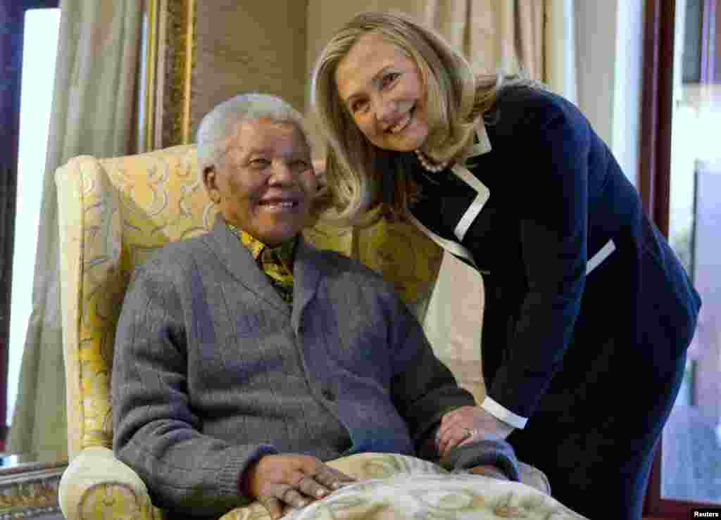 Secretary of State Hillary Clinton poses for a photograph with Nelson Mandela (left), former president of South Africa, at his home in Qunu on August 6, 2012.