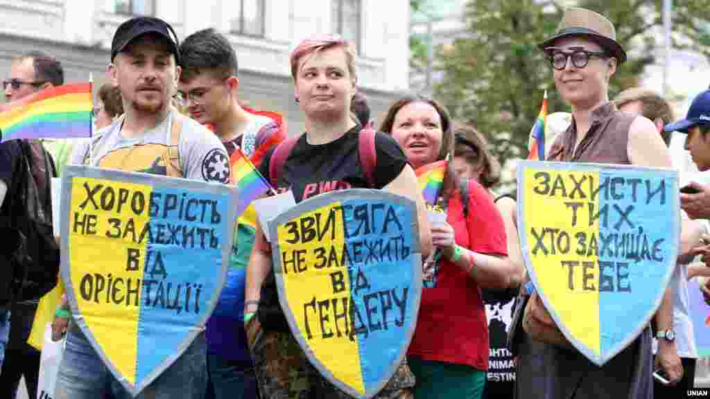 "Marchers with pro-LGBT signs on the colors of the Ukrainian flag. (From left to right: ""Bravery doesn't depend on your orientation.""/""Victory doesn't depend on gender.""/""Protect those who protect you."")"