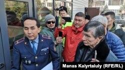 Банктегі есепшоты бұғатталған белсенділер полиция департаменті алдында полиция өкіліне сұрақ қойып тұр. Алматы, 12 наурыз 2020 жыл.