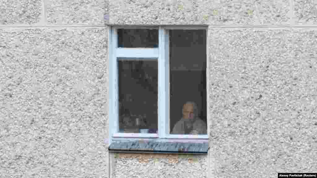Літній чоловік дивиться у вікно свого будинку в Євпаторії