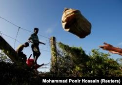 Беженцы рохинджа перебрасывают вещи через забор на границе Мьянмы с Бангладеш, 29 августа 2017 года