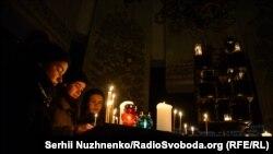Люди ставят свечи на алтарь в День памяти жертв голодомора. Киев, 26 ноября 2016 года.