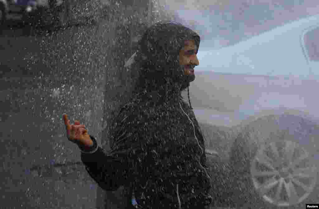 A demonstrator in Diyarbakir gestures as riot police use a water cannon to disperse the crowd during a protest against the arrest of the Kurdish-dominated Turkish city's two joint mayors for alleged links to terrorism. (Reuters/Sertac Kayar)